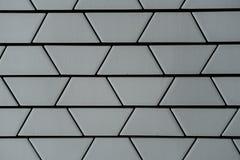 Närbild av den dekorativa keramiska vita tegelstenväggen i den passande trapetsoiden Arkivfoto