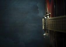 Närbild av den gamla elektriska jazzgitarren på ett mörker - blå bakgrund Arkivfoton