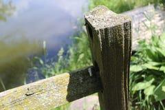 Närbild av den gamla staketstolpen framme av vatten Royaltyfri Bild