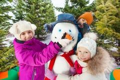 Närbild av den gladlynta snögubben för lyckligt barnbyggande fotografering för bildbyråer