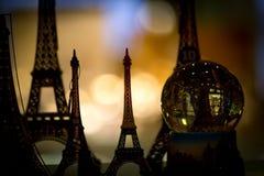 Närbild av den glass sfären och Eiffeltornkopior arkivfoto