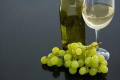 Närbild av den gröna gruppen av druvor med exponeringsglas och flaskan av vin Royaltyfria Foton