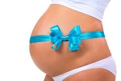 Närbild av den gravida buken med strumpebandsorden och pilbågen Begrepp av havandeskap behandla som ett barn den nyfödda pojken Arkivbild