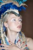 Närbild av den härliga unga kvinnan med den befjädrade huvudbonaden Fotografering för Bildbyråer