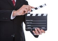 Närbild av den hållande clapperboarden för man Fotografering för Bildbyråer