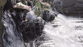 Närbild av den heliga strömmen för vårvatten som häller in i pölen och den traditionella BalineseofferingsCanang sari som göras a arkivfilmer