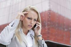 Närbild av den ilskna affärskvinnan som samtalar på mobiltelefonen mot kontorsbyggnad arkivbilder