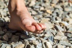 Närbild av den kala foten som går på stenar, utomhus aktivitet Royaltyfria Bilder