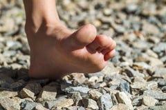 Närbild av den kala foten som går på stenar, utomhus aktivitet arkivbild