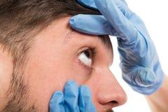 Närbild av den kvinnliga doktorn som kontrollerar det manliga tålmodiga ögat Arkivbilder