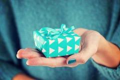 Närbild av den kvinnliga handen som rymmer en gåva Fotografering för Bildbyråer