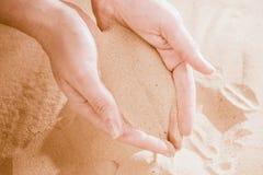 Närbild av den kvinnliga handen som släpper tappa sand Sand som flödar till och med händerna Royaltyfria Bilder