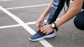 Närbild av den kvinnliga löparen som snör åt henne skor arkivbild