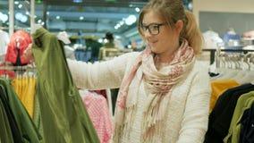 Närbild av den kvinnliga shopparen, val av modekläder av olika färger på hängare, ung attraktiv naturlig blondin arkivfilmer