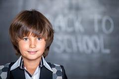 Närbild av den lilla skolapojken nära svart tavla Royaltyfri Foto