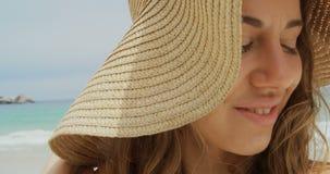 Närbild av den lyckliga Caucasian kvinnan i hatten som står på stranden 4k arkivfilmer