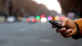 Närbild av den manliga handen genom att använda mobiltelefonen nära huvudvägen Bokeh av bilbillyktor arkivfilmer
