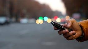 Närbild av den manliga handen genom att använda mobiltelefonen nära huvudvägen Bokeh av bilbillyktor lager videofilmer