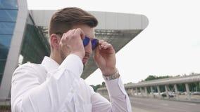 Närbild av den manliga modellen för stiligt mode som tar på hans solglasögon och blickar till kameran Stads- stadsbakgrund lager videofilmer