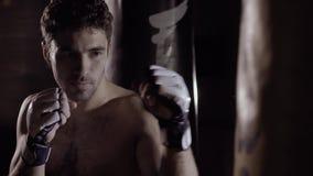 Närbild av den muskulösa mannen som slår boxningpåsen arkivfilmer