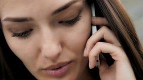 Närbild av den nätta brunettaffärskvinnan som i regeringsställning talar på telefonen, härlig arabisk konsulent arkivfilmer