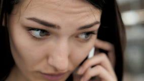 Närbild av den nätta brunettaffärskvinnan som i regeringsställning talar på telefonen, härlig arabisk konsulent lager videofilmer