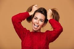 Närbild av den roliga unga unga flickan som visar hennes tunga, hållande H Arkivfoto