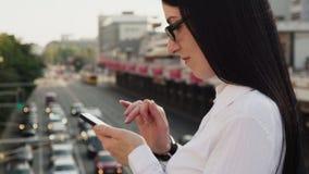 Närbild av den säkra affärskvinnan som använder smartphonen som arbetar på stadsgatan arkivfilmer