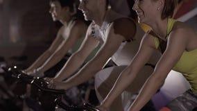 Närbild av den sportiga gruppen som gör cardio utbildning i idrottshallen