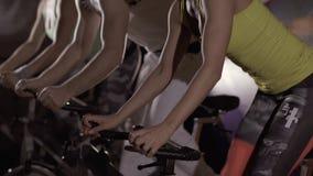 Närbild av den sportiga mannen och två unga kvinnor som övar deras ben på stationära cyklar lager videofilmer