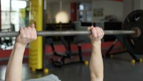 Närbild av den starka idrottsman nen som lyfter skivstången på idrottshallen, tyngdlyftning, sport stock video