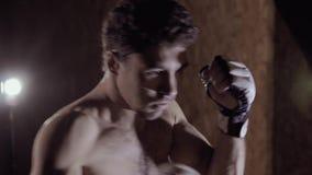 Närbild av den starka mässa-flådde koncentrerade mannen som utarbetar genom att använda stansmaskinsäcken arkivfilmer