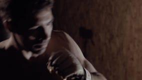 Närbild av den starka sunda mannen som utarbetar entusiastiskt genom att använda boxningpåsen lager videofilmer