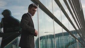 Närbild av den stiliga säkra affärsmannen i exponeringsglas som väntar på hans flyg Glass flygplatsväggbakgrund stock video