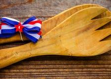 N?rbild av den stora tr?tj?nande som gaffeln och skeden med den r?da, vita och bl?a pilb?gen royaltyfria foton