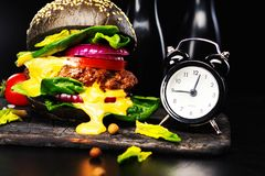 Närbild av den svarta nötkötthamburgaren med den flödande smältta ost och klockan på en svart bakgrund royaltyfri foto