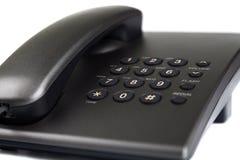 Närbild av den svarta skrivbords- telefonen Arkivfoto