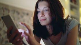 Närbild av den unga le kvinnan som använder smartphonen som hemma ligger i säng på natten