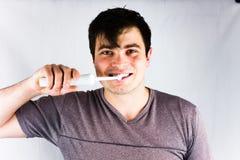 Närbild av den unga mannen som borstar tänder med den elektriska tandborsten Glad ung man som ler under att borsta för morgontänd Arkivbild