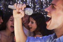 Närbild av den unga mannen som rymmer en mikrofon och sjunger på karaoke, vänner som sjunger i bakgrunden Arkivbilder