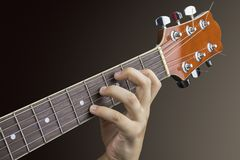 Närbild av den vänstra handen av en ung gitarrist på halsen av en akustisk gitarr arkivbilder