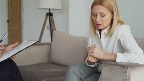 Närbild av den vuxna kvinnan som gör en gest nervöst händer, medan tala till den manliga psykologen i regeringsställning lager videofilmer