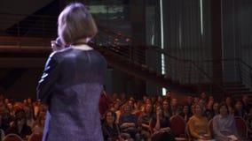 Närbild av den vuxna kvinnliga högtalaren med kort hår, i ett grått klänninganseende på etapp och att anmäla för åhörare konst fotografering för bildbyråer
