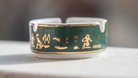 Närbild av det guld- askfatet, med oskarp bakgrund Royaltyfri Fotografi