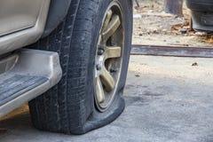 Närbild av det skadade plana gummihjulet av bilen på parkering arkivfoto
