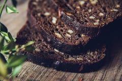 Närbild av det skivade bruna brödet på skärbrädan på trätabellen med svart bakgrund Detaljerad närbild royaltyfri fotografi