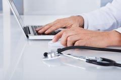 Närbild av doktorn som använder bärbara datorn Fotografering för Bildbyråer