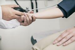 Närbild av doktorn som kontrollerar blodtryck på armen royaltyfri bild