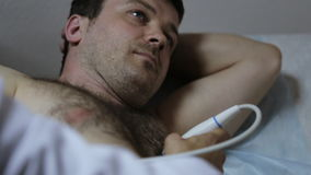 Närbild av doktorshanden som gör den medicinska ultraljudmanpatienten lager videofilmer