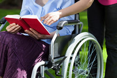 Närbild av en äldre kvinna i en rullstol som läser en bok Royaltyfria Bilder
